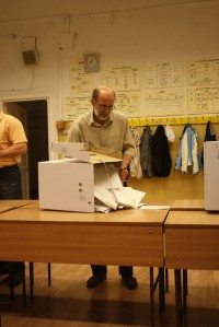 A poll worker opens a ballot box to begin vote-counting, 6 April.